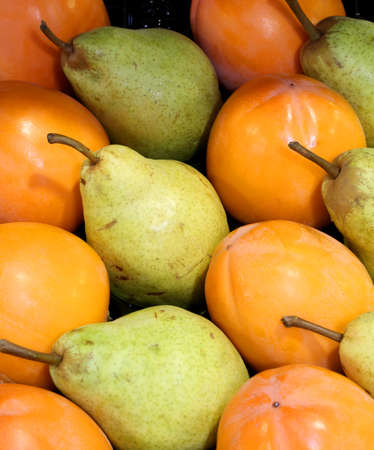 fruit background with green pears and orange persimmon