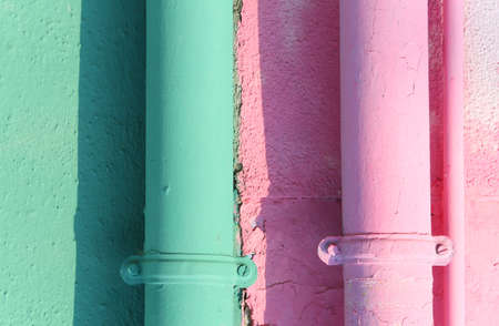 two colored gutters on the painted wall of the house in Burano Island near Venice Italy