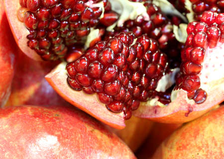 background of many pomegranate fruits with red seeds inside the typical autumn fruit