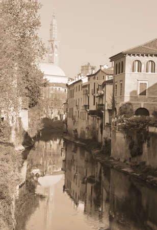 reflected on the river called RETRONE of the tower of the most important monument of the city of Vicenza in Northern Italy with sepia toned effect Banco de Imagens
