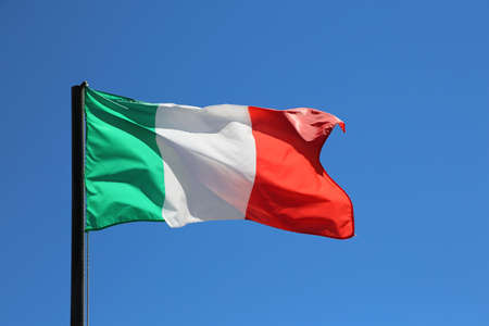 Big Italian flag waving in blue sky with red and white green colors