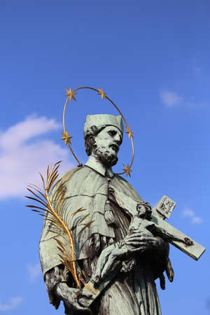 Bronze statue of John Nepomucene with halo and crucifix Editorial