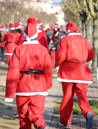 people  with red dress of Santa Claus during the race at Christmas in the public park Stock Photo