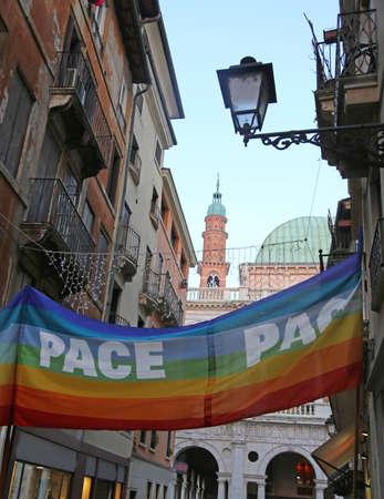 イタリア語で平和を意味するテキストPACEと狭いヴィア・デッラ・チッタ・ディ・ヴィチェンツァの大きな多色の旗 写真素材