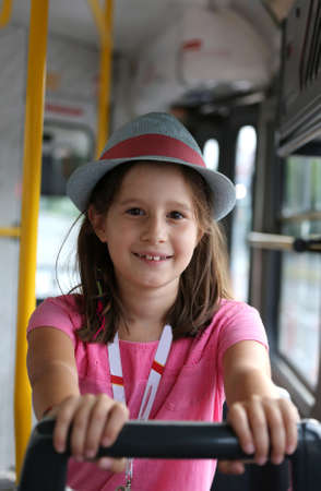 smiling little girl with hat in the tram