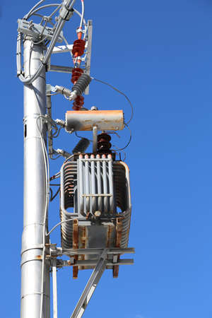 steel pole with electric transformer and high voltage electrical cables and blue sky in background Stock Photo