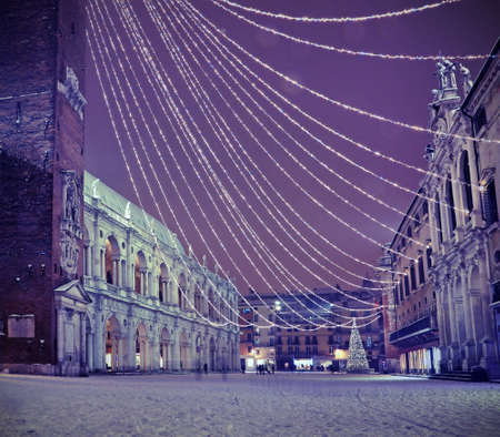 Vicenza in Italy by night. the main Square called Piazza dei Signori with snow and Christmas lights with vintage effect and snowflakes