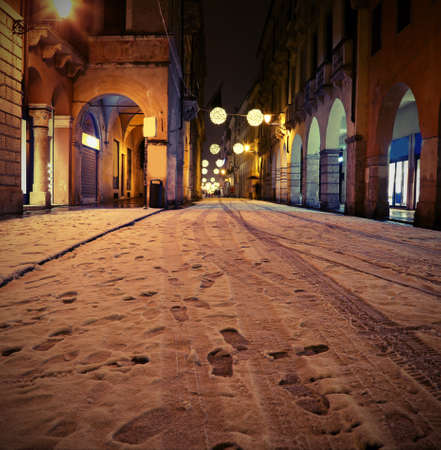 Main street in downtown called CORSO PALLADIO of Vicenza City in Italy with vintage effect and snow by night