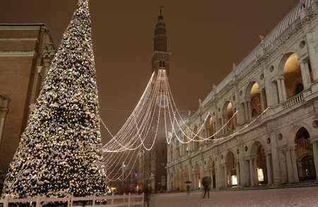 Vicenza in Italy Main square with snow and the most famous monument called Basilica Palladiana headquarters of the temporary exhibition of van Gogh paintings and a very big xmas Tree by night 스톡 콘텐츠