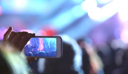 young girl takes a photo with the technology smartphone during the live concert