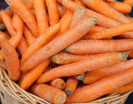 many orange organic carrots in wicker basket