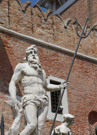 statue of Neptune with the trident near the building called Arsenal of Venice in Italy Imagens