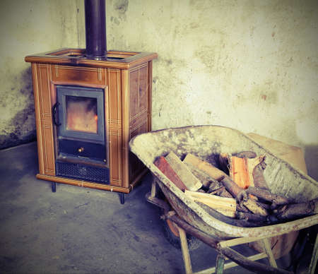ancient tiled stove and wheelbarrow full of firewood to heat the mountain house with vintage effect Stock Photo