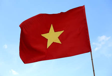 big flag of Vietnam with big yellow star in the red background with blue sky