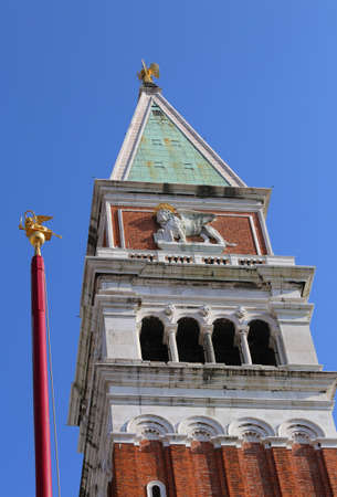Detail of ancient bell tower of Saint Mark with winged lion and the small golden lion on top of the red pole in Venice Island in Italy