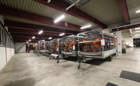 Vicenza, Italy - January 1, 2017: Wide warehouse inside the headquarters of main italian tour operator called Girolibero with many orange bicycles ready for tourist