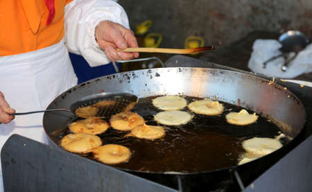 Chef Cooks many pancake made with apples in a big pot full of olive oil Foto de archivo