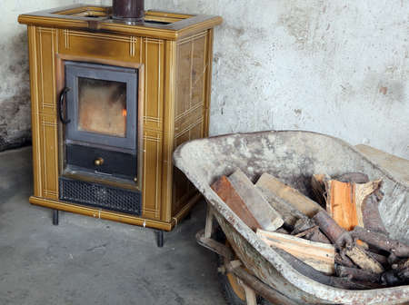 ancient tiled stove and wheelbarrow full of firewood to heat the old mountain house Stock fotó