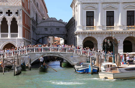 Venice, Italy - July 14, 2016: Ancient Bridge of Sighs and ancient Ducal Palace with many people on the Bridge called PONTE DELLA PAGLIA in Italian Language