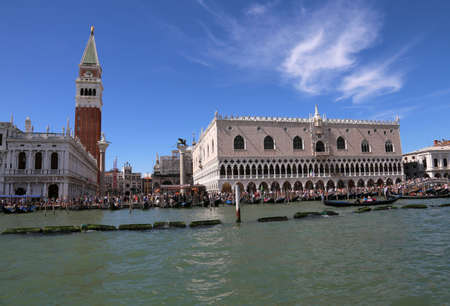 Venice, Italy - July 14, 2016: Saint Mark Bell Tower called CAMPANILE DI SAN MARCO in Italian Language and the ancient Ducal Palace