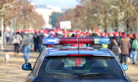 police car during the manifestation with many people in the public park