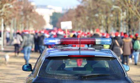 politie-auto tijdens de manifestatie met veel mensen in het openbare park