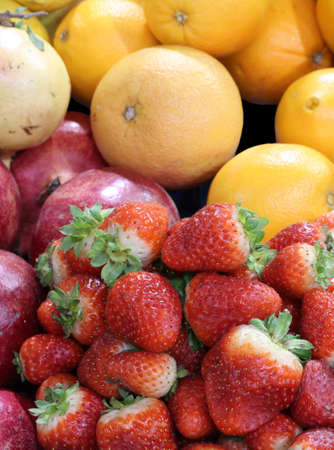 background of fresh fruit with strawberries pomegranes oranges grapefruits Stock Photo