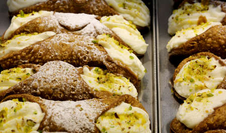 many Sicilian cannoli stuffed with ricotta cheese and pistachios
