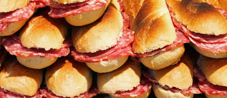background of many stuffed sandwiches with sliced salami
