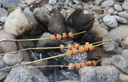 bonfire with stones to cook wurstel flavors during the boy scout camp Stock Photo
