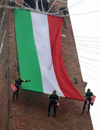 Vicenza, Italy - December 4, 2015:  many brave firefighter unroll italian flag on the ancient tower called Torre Bissara during a commemorative event