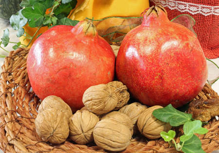 wicker basket with two ripe pomegranates and walnuts Stock Photo