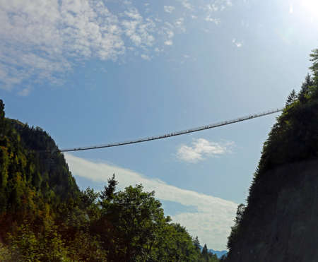 very long suspension bridge between two mountains with many adventurous intrepid people crossing it Banco de Imagens