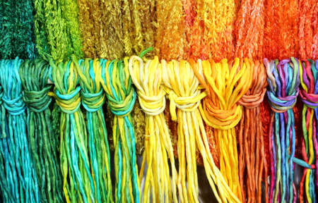 many colorful threads of knotted and woven fabric Stock Photo