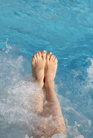 feet of the young woman during the hydromassage session to reactivate the blood circulation in the spa