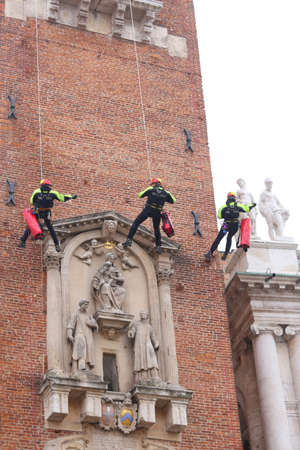 Vicenza, Italy - December 4, 2015:three brave firefighters climb the high tower into the main square of the city during a check Editorial