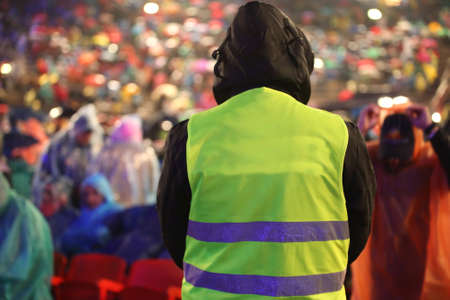 Security guard with safety vest controls people during an important event while it is raining Banque d'images