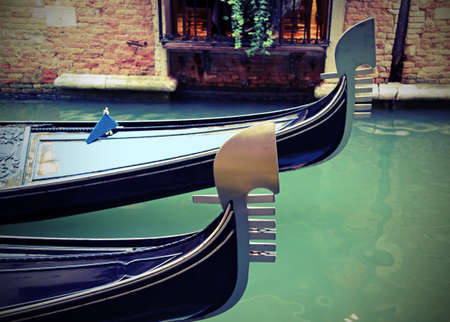 Venice in Italy and the bow of the two famous gondolas on the waterway