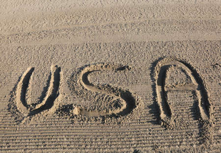 big text WORD USA United States of America on the sand of the beach