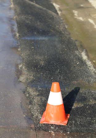 road cone used to asphalt demarcation during road asphalting works Imagens