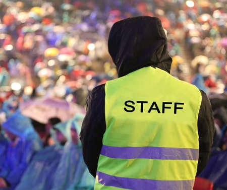 security guard with safety vest with STAFF inscription controls people during an important event during a rainstorm