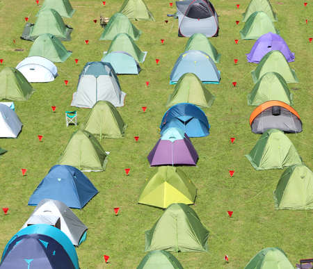 Colorful camping tents mounted in a lush green lawn