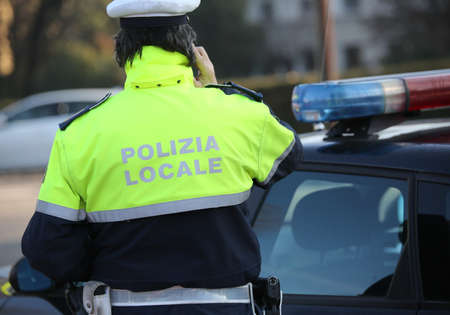 警官は市内のパトカーの近くで電話をしています。テキストポリツィアロケールは、イタリア語で都市のローカル警察を意味します