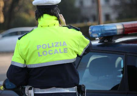 Polizist ruft in der Nähe des Polizeiautos in einer Stadt an. Der Text Polizia Locale bedeutet die lokale Polizei der Stadt in italienischer Sprache Standard-Bild