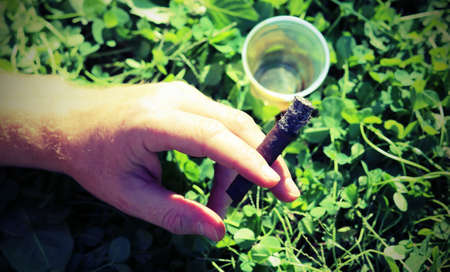 young chain smoker with cigar in hand and plastic glass of wine  with vintage style effect