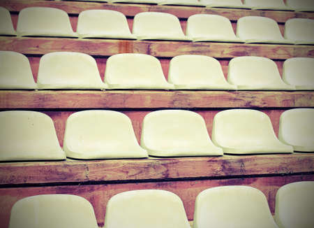 White seats on stadium bleachers without  people before the meeting sports with vintage effect Banco de Imagens