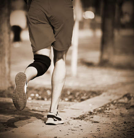 young athlete runs the race with the knee bandage with sepia toned
