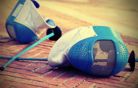equipment fencing mask and foil resting on the ground after the defeat of the sport event with vintage effect