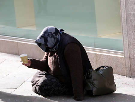 elderly poor Gypsy woman begs for alms lying in the street