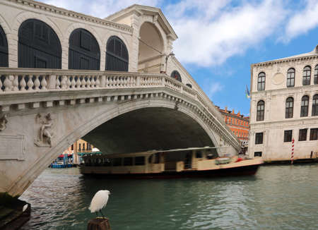 famous Rialto bridge in Venice with the vaporetto moving on the Grand Canal